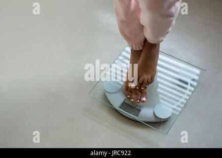 Low section of woman standing on bathroom scale at home - Stock Photo
