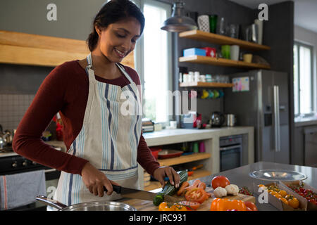 Smiling woman cutting zucchini in kitchen at home - Stock Photo