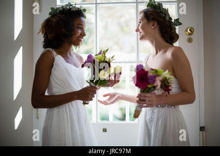 Bride and bridesmaids standing with bouquet at home - Stock Photo