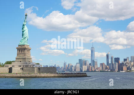 Statue of Liberty island and New York city skyline in a sunny day, white clouds - Stock Photo