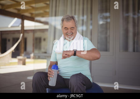 Senior man checking time on wristwatch after work out at veranda - Stock Photo
