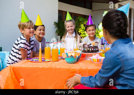 Friends talking while sitting at table during birthday party in yard - Stock Photo