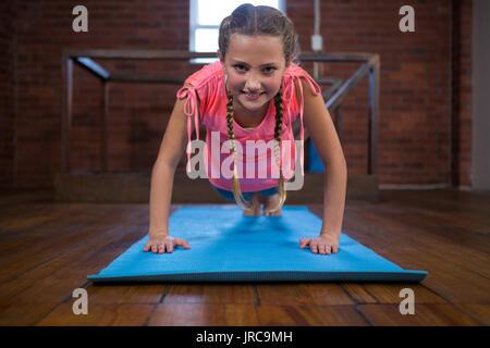 Portrait of happy teenage girl doing pushup in fitness studio - Stock Photo