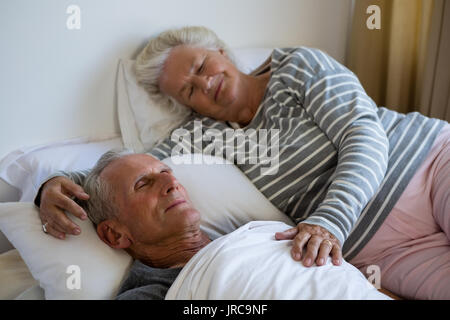 High angle view of senior couple sleeping on bed in nursing home - Stock Photo