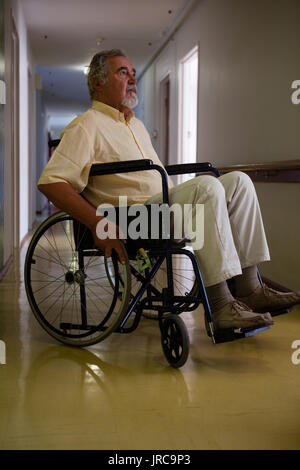 Thoughtful senior man sitting on wheelchair in corridor at retirement home - Stock Photo
