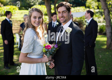 Portrait of happy bride and groom standing in park - Stock Photo