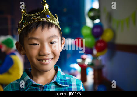 Portrait of boy wearing crown during party - Stock Photo
