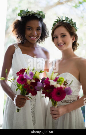 Portrait of bride and bridesmaids standing with bouquet at home - Stock Photo