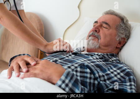 Cropped hands of doctor listening to heartbeats of senior man sleeping on bed in retirement home - Stock Photo