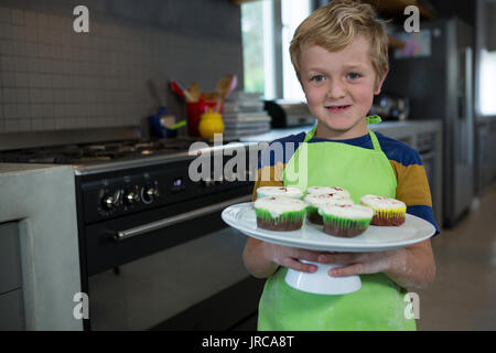 Portrait of boy holding plate with cupcakes in kitchen at home - Stock Photo