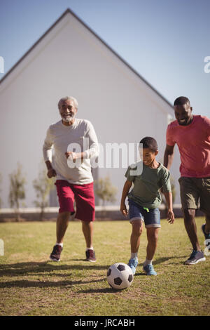Boy playing football with his father and grandson in garden - Stock Photo