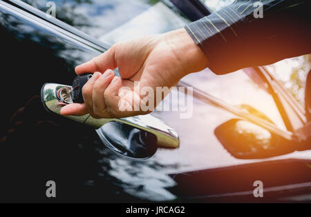Close-up of man opening a car door. Hand on handle. Businessman is opening a car. - Stock Photo