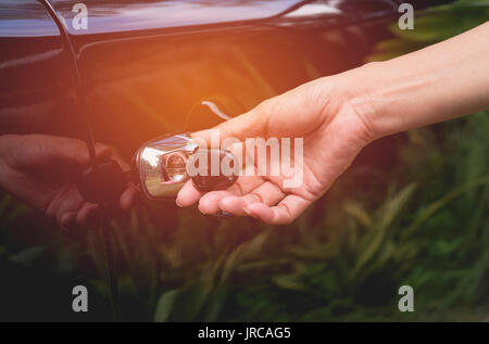 Close-up of woman opening a car door. Hand on handle. Female is opening a car. - Stock Photo