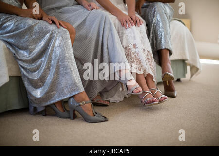 Bride and bridesmaids sitting together on sofa at home - Stock Photo