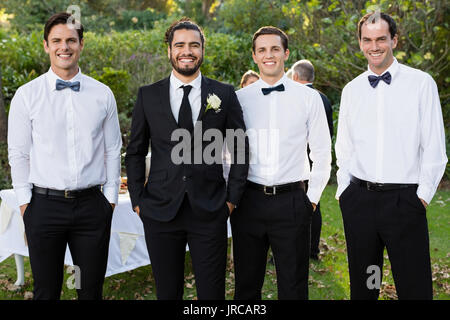 Portrait of smiling groom and groomsmen standing with hands in pocket - Stock Photo