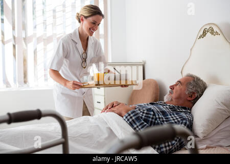 Female doctor serving food to senior patient relaxing on bed in nursing home - Stock Photo