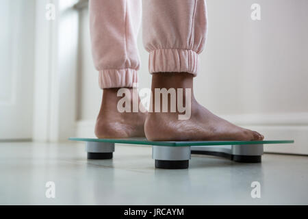 Low section of woman standing on bathroom scale - Stock Photo