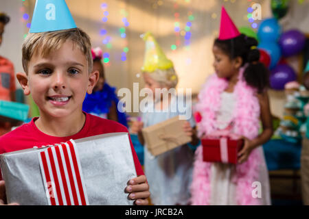 Portrait of happy boy showing gift with friends in background - Stock Photo