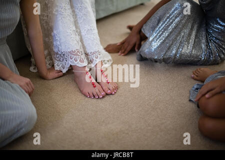 Bride and bridesmaids sitting together at home - Stock Photo