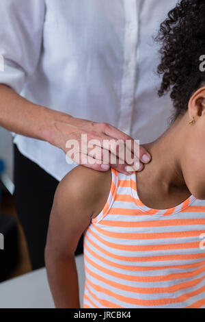 Mid-section of physiotherapist giving neck massage to girl patient in clinic - Stock Photo
