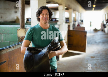Mature man working in the stable - Stock Photo