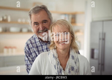 Portrait of senior couple hugging each other at home - Stock Photo