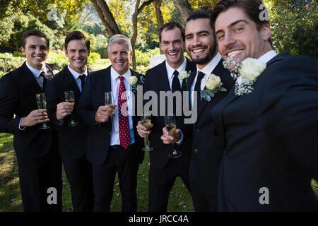 Portrait of groom and groomsmen having champagne in park - Stock Photo