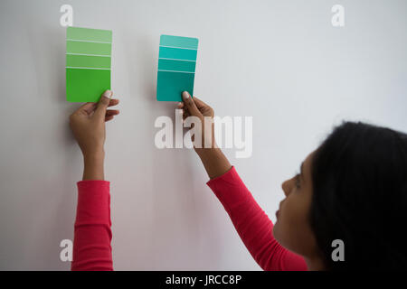 Young woman holding color swatches by wall at home - Stock Photo