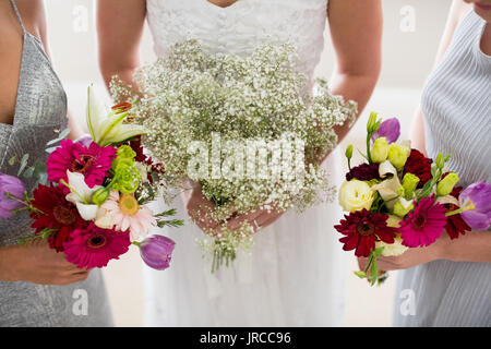 Mid section of bride and bridesmaids standing with bouquet at home - Stock Photo