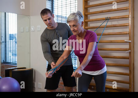 Male physiotherapist helping patient in performing exercise with resistance band in clinic - Stock Photo