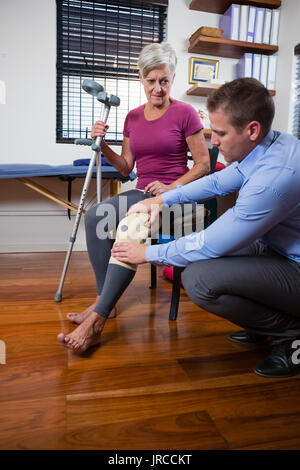 Physiotherapist examining senior patient knee in clinic