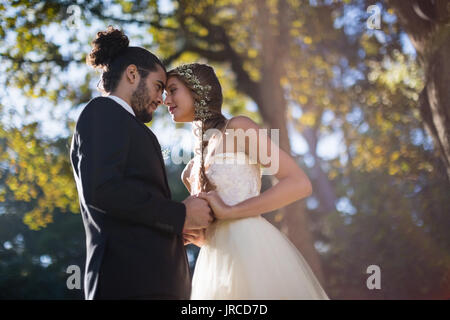 Affectionate couple dancing in park during wedding - Stock Photo