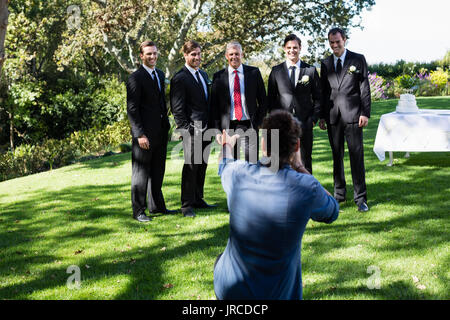 Photographer taking photo of groom and groomsmen at park - Stock Photo