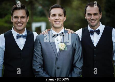 Portrait of smiling bridegroom and best man standing in garden - Stock Photo