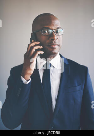 Portrait of a confident young African businessman wearing a suit and glasses talking on a cellphone while standing - Stock Photo