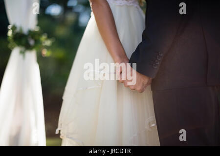 Mid section of couple holding hands in park - Stock Photo