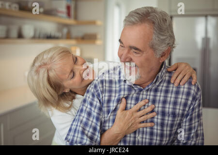 Senior couple hugging each other at home - Stock Photo