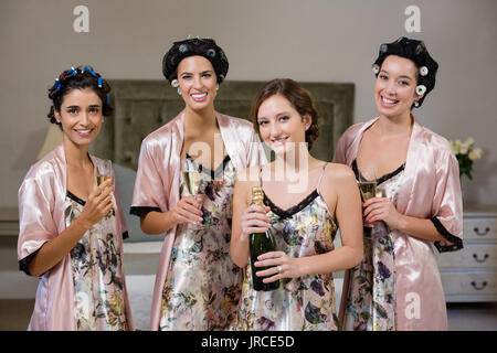Portrait of women holding glasses of champagne at home - Stock Photo