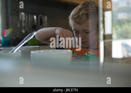 Boy decorating cupcakes with sprinklers seen through glass in kitchen - Stock Photo