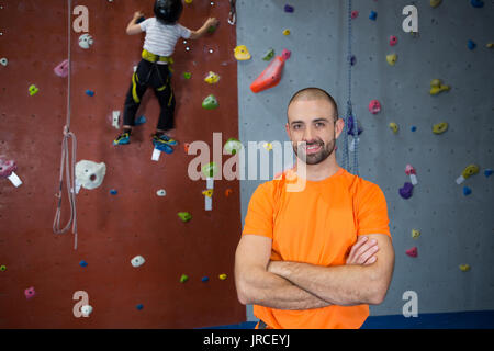 Portrait of trainer standing with arms crossed in fitness studio - Stock Photo