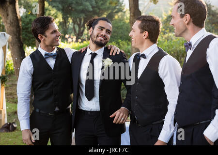 Happy groom and groomsmen having fun in park - Stock Photo