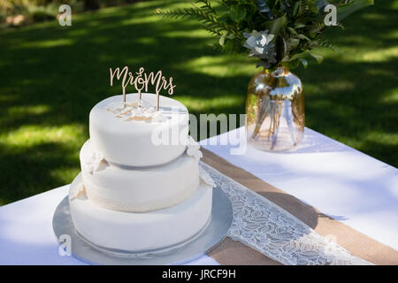 Decorated wedding cake on table in park - Stock Photo