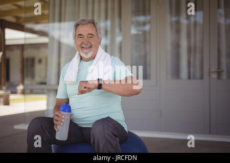 Smiling senior man checking time on wristwatch after work out at veranda - Stock Photo