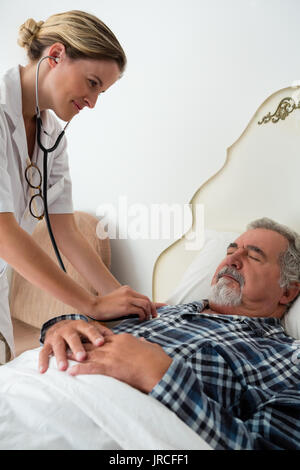Female doctor listening to heartbeats of senior man sleeping on bed in retirement home - Stock Photo
