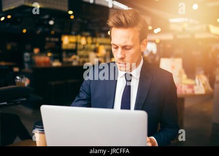 Young businessman in a suit sitting alone at a table in a cafe drinking a coffee and working online with a laptop - Stock Photo