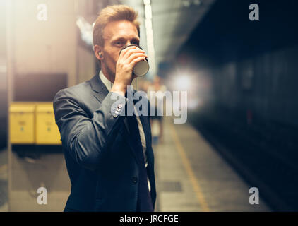 Young businessman drinking a coffee and listening to music on his cellphone while standing on a subway platform - Stock Photo