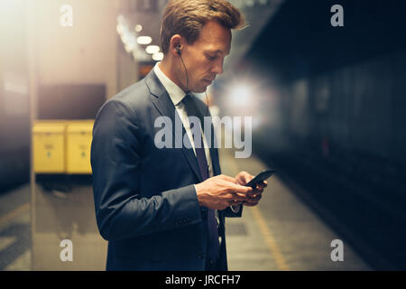 Young businessman wearing earphones and reading text messages on his cellphone while standing on a subway platform - Stock Photo