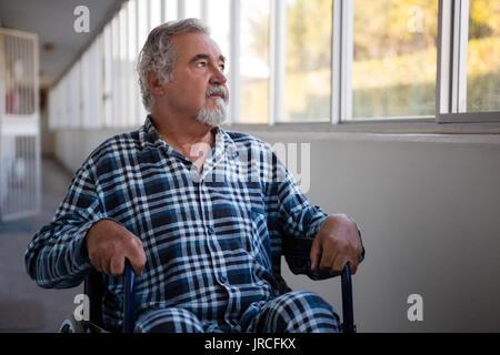 Thoughtful senior man looking through window while sitting on wheelchair in nursing home - Stock Photo