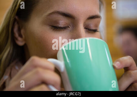 Close up of young woman with eyes closed drinking coffee at cafe - Stock Photo