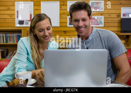 Happy couple using laptop while sitting in coffee shop - Stock Photo